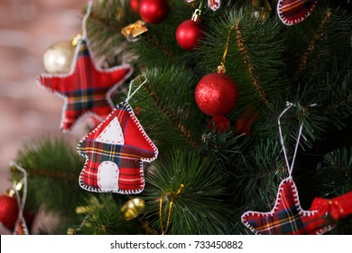 Christmas green pine tree decorated with red colorful toys stars balls sox and horse in studio shoot scene of new year holiday decorations.