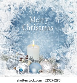 Christmas greeting background with candles, pine branches, balls on a blue background with a frosty pattern