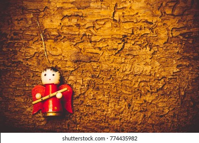 Christmas greeting background. Cute angel musician figurine on old wooden background with copy space.