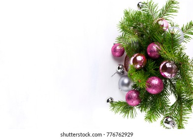 Christmas greeting background with fir branches, glitter, pink and silver baubles wreath, copy space
