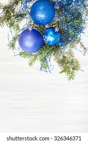 Christmas greeting card - border from three blue and violet Xmas baubles and tree branch on blank paper background