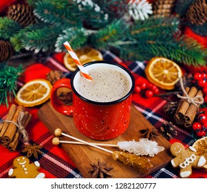 Christmas greeting card. Cacao drink in enamel cup with fir branches, dried orange slices, red berries, spices and gingerbread man on red fabric background.