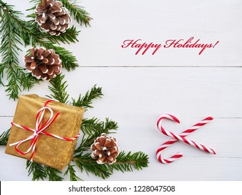 Christmas greeting card with candy cane, gift, cones and fir branches over white wooden background.
