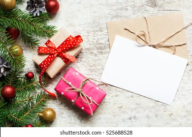 christmas greeting card with envelope on white wooden background with fir tree branches and happy new year decorations