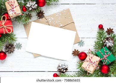 christmas greeting card with fir tree branches, decorations and gift boxes over white wooden background. mock up. flat lay