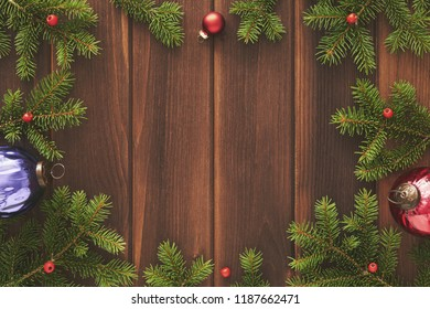 Christmas greeting card frame with place for your text. Decorations of green fir branches, red glass Christmas balls, beads against a background of brown old worn wooden boards