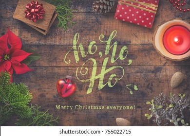 Christmas greeting card with gifts, fir tree twigs, poinsettia a heart-shaped bauble and a candle on a wooden background - subtle vintage effect