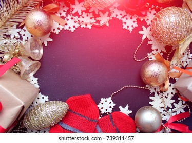 Christmas greeting card. Gold and red Christmas decorations, mittens on a dark background. Copy space.