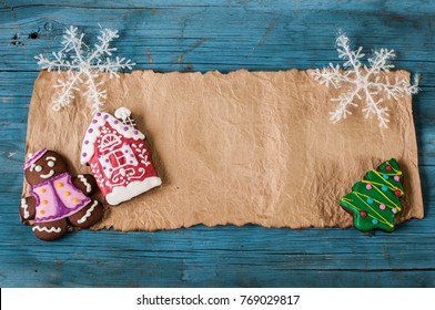Christmas greeting card, old blank paper sheet, ginger cookies on wooden background
