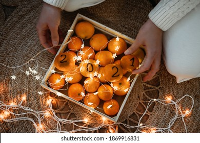 Christmas greeting card with oranges, tangerines with numbers 2021 and garland lights. New Year 2021 is Coming, Cozy Christmas Concept. Black Numbers 2021 written on Oranges.