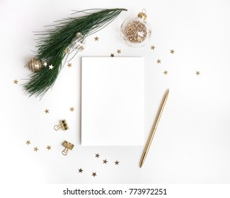 Christmas greeting card template in gold. Empty paper mock up, fir tree branch with glass ball decorations, star confetti, pen on white background. New year flat lay, top view, copy space
