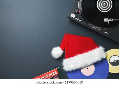 Christmas greeting card. Vinyl record frame with black vinyl record, purple and yellow vinyl records, red Santa Claus hat on a dark blue background with space for your text and design.