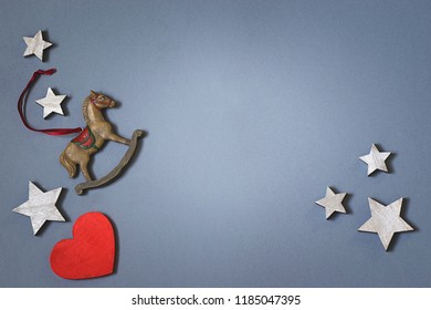 Christmas greeting card for the winter holidays. Wooden heart, small wooden hourse  and silver stars on the blue gray background, moke up. Flat lay
