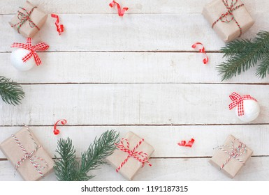 Christmas greeting card wrapped gift box, fir branches, balls on white wooden table, top view, New Year border, flat lay
