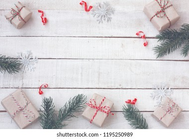 Christmas greeting card wrapped gift box fir branches, balls, silver snowflakes on white wooden table, top view, New Year border