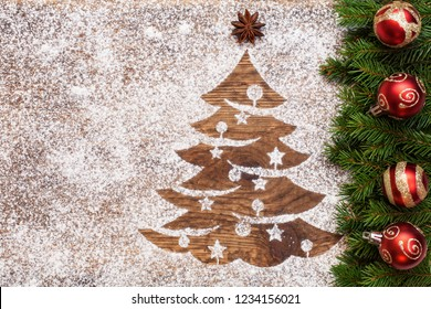Christmas greeting with xmas tree drawing in flour and fir branches with decorations