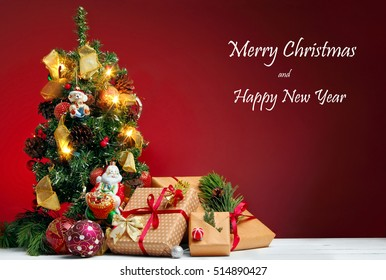 Christmas greetings card.Christmas tree with gifts on red background.