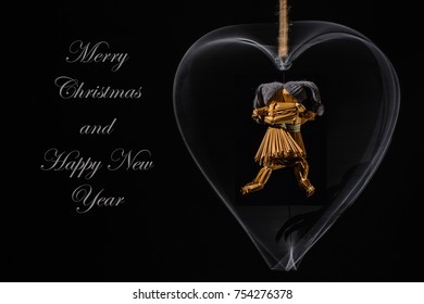 Christmas greetings with dancing straw dolls in a rotating metal heart and with the text: Merry Christmas and Happy New Year