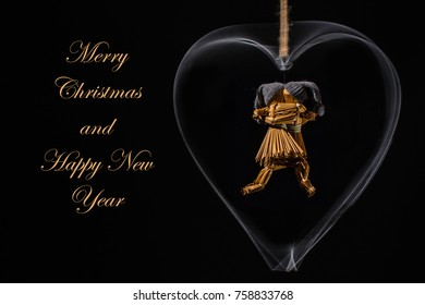 Christmas greetings with dancing straw dolls in a rotating metal heart and with the text: Merry Christmas and Happy New Year in straw/gold color