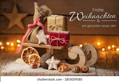 Christmas greetings in German - small sleigh with presents and lights on wood