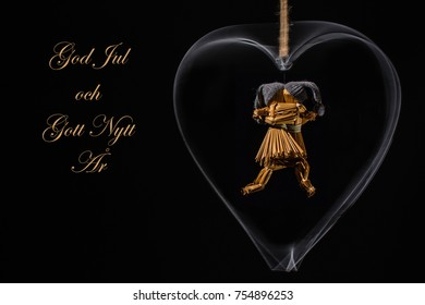 Christmas greetings in Swedish with dancing straw dolls in a rotating metal heart and with the text: God Jul och Gott Nytt Ar (=Merry Christmas and Happy New Year)