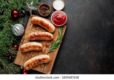 Christmas grilled sausages with spices on a stone background with Christmas trees and Christmas decorations, gifts  				with copy space