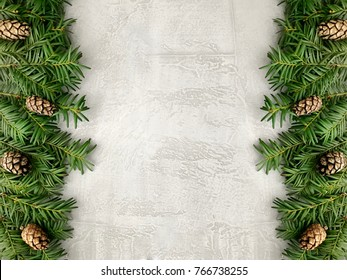 Christmas grunge background with fir branches and pine cones. Floral New Year frame. Border with copy space.