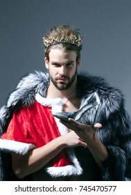 Christmas guy in santa fur coat in crown. Drag queen, homosexual and trans. Cinderella prince with shoe on grey background. Freak, gay and transvestite. Freedom and lgbt, kitsch.