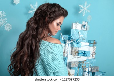 Christmas hairstyle. Portrait of attractive woman with wedding wavy hair style. Beautiful brunette girl with long hair wears in warm turquoise woolen sweater over Christmas tree and xmas decorations.