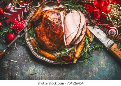 Christmas ham served with roasted vegetables and festive decorations on vintage background in retro color, top view, place for text. Christmas recipes and dishes concept