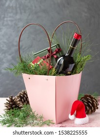 Christmas hamper with bottle of wine and gifts in boxes. Paper basket, no plastic concept. Holiday decoration