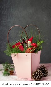 Christmas hamper. Pink paper basket with festive goodies and gifts. Vertical orientation, copy space