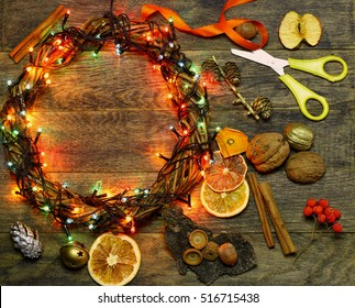 Christmas hand made craft template background. Make traditional New Year`s door wreath components: tree cones, dried oranges, cinnamon, ribbon and colorful garland lights. Copyspace for text.