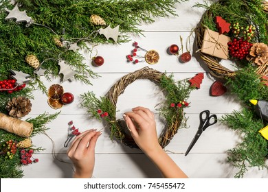Christmas handmade diy background. Making craft xmas wreath and ornaments. Top view of white wooden table with female hands.