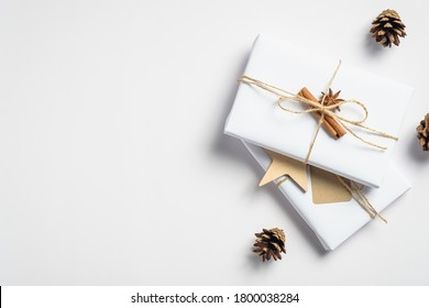 Christmas handmade gift box wrapped eco friendly packaging paper and decorations on white background. Merry Christmas greeting card mockup.