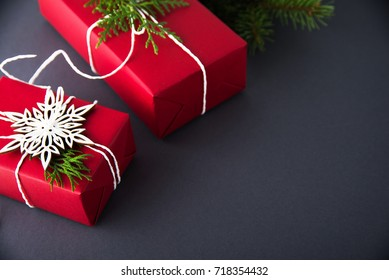 Christmas handmade gift boxes decorated with red paper and white snowflakes on dark grey background. Merry christmas greeting card. Winter xmas holiday theme. Happy New Year.
