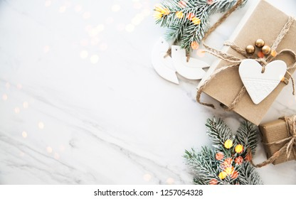 Christmas handmade gift boxes on white marble background top view. Merry Christmas greeting card, frame. Winter xmas holiday theme. Noel. Happy New Year. Flat lay