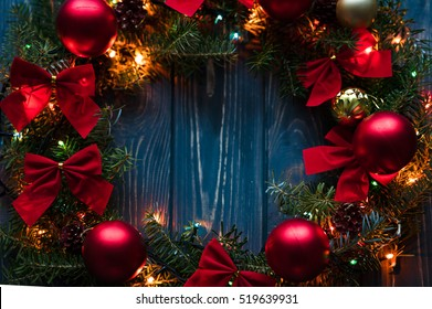 Christmas handmade wreath on a wooden background. Festive lights of garland. Interior decoration