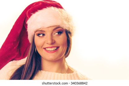 Christmas happiness concept. Portrait of smiling beautiful thinking woman in santa hat.