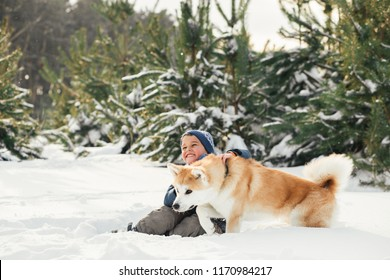 Christmas happy child boy running playing with Akita-Inu dog on white snow in winter day. A happy boy hugging his beloved dog, playing in the snow-covered forest.