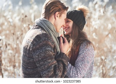 christmas happy couple in love embrace in snowy winter cold forest, copy space, new year party celebration, holiday and vacation, travel, love and relations.