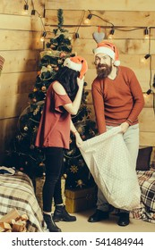 christmas happy couple in red santa claus hat and sweater hold present sack at xmas decorated tree. bearded man with cute pretty girl at new year holidays celebration