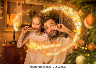 Christmas happy family time - carefree caucasian father and daughter playing (clowning) around while holding candy canes. Moody warm (gold) light, magical sparkles, cozy atmosphere in decorated room.