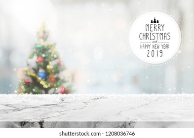 Christmas and Happy new year 2019 on empty white marble stone table top on blur bokeh christmas tree background with snowfall - can be used for display or montage your products.