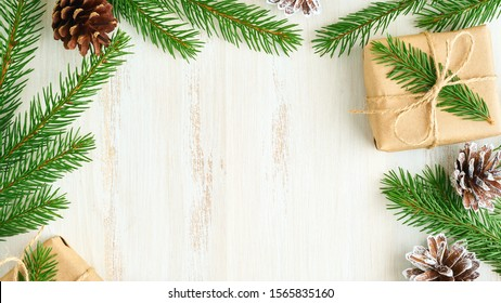 Christmas and Happy New Year zero waste wooden background. Handmade gift Christmas box, fir branches, craft paper , top view, copy space. Ecofriendly plastic free concept