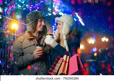 Christmas. Happy young couple after shopping with bags of gifts on a winter evening drinking coffee from disposable cups on a city street. Xmas, Holidays, People.