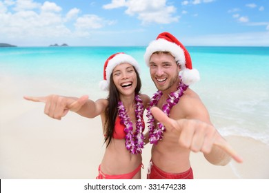 Christmas Hawaii vacation - Hawaiian beach couple wearing santa hat and doing welcome shaka sign happy at camera as welcoming gesture for winter holidays.