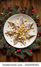 Christmas Herrings fillets with apples, pickled cucumbers, red onion and spices on a ceramic plate on a festive decorated wooden table, top view. Christmas, traditional dish