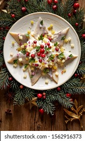 Christmas Herrings fillets with cream sauce with apple, pickled cucumbers, red onion and spices, garnished with cranberries on a ceramic plate on a festive decorated wooden table, close-up.