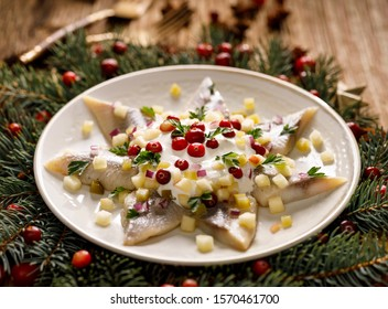 Christmas Herrings fillets with cream sauce with apple, pickled cucumbers, red onion and spices, garnished with cranberries on a ceramic plate on a festive decorated wooden table. Traditional dish.